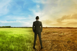 Businessman standing between different climates, global warming effecting business