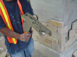 man-installing-adhered-masonry-veneer